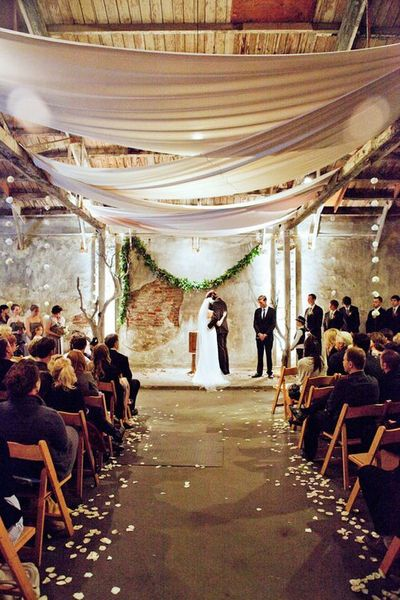 Warehouse wedding, draped fabric, exposed brick, wood... love the drape over the aisle