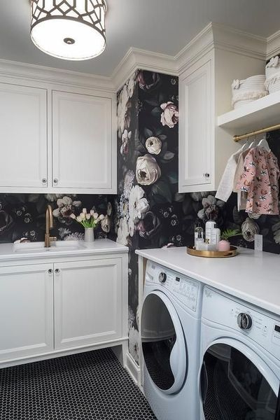 Romantic Ellie Cashman Dark Floral Wallpaper covers the wall of this elegant white laundry room illuminated by a trellis flush mount fixed over black hexagon floor tiles.