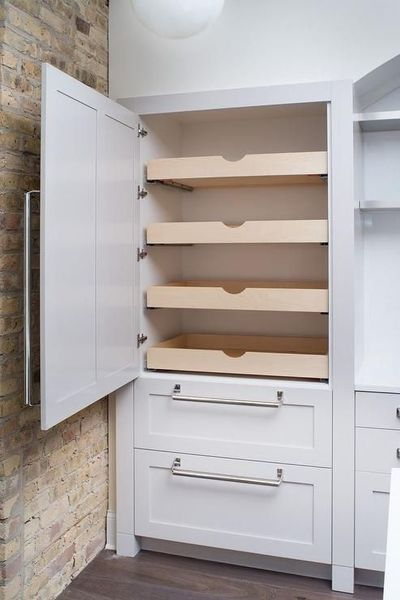 Fabulous kitchen features concealed pantry cabinets fitted with stacked pull out drawers next to an exposed brick wall.