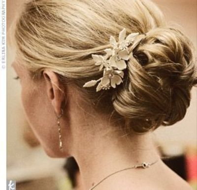 A beautiful, ivory, enamel hair comb with two flowers and Swarovski crystals accented the low, loosely gathered bun.