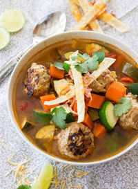 Albondigas Mexican Meatball Soup Recipe: olive oil, red and yellow bell peppers, onion, garlic, yellow chile, jalapeno, Mexican style diced tomatoes, chicken broth, beef broth, lime juice, adobo chili peppers, fresh cilantro, carrots, zucchini, onion powd...
