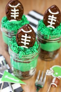 It's Super Bowl Party time! Enjoy the big game with this mason jar brownie sundae! Brownies in the shape of footballs top layers of luscious buttercream and fud
