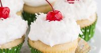 Coconut Tres Leches Cupcakes- Vanilla cupcakes infused with three milks and topped with homemade whipped cream, coconut, and cherries.