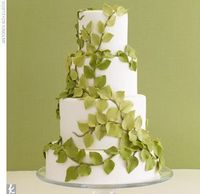 Four-tiered white fondant wedding cake covered with green sugar-made leaves.