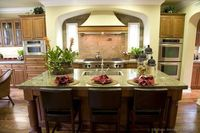 This luxury kitchen has a warm color scheme, a large island, and beautiful Seafoam Green granite countertops. (Kitchen-Design-Ideas.org)