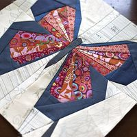 Machine paper piecing a butterfly quilt block using low volume scraps for the background and bright pinks and blues for the butterfly.