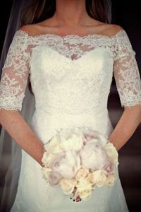 Removable lace sleeves over strapless dress for ceremony.