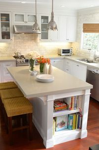 L shaped kitchen with creamy shaker kitchen cabinets paired with gray quartz countertops and beveled marble subway tile backsplash. Restoration Hardware Benson Pendants over white kitchen island with corbels and built-in bookcase filled with cookbooks. Wh...