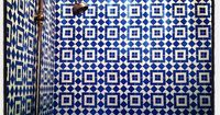 Fabulous blue and white patterned tiles and a brass showerhead. Simple but striking bathroom!