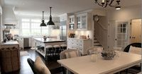 Open, airy kitchen. Some design elements I love: mix of glass-door cabinets and open shelves help keep this large room cottage-like and give it personality as do legs on bottom cabinets. Dark wood floors offers great contrast to all the white. So much cha...