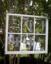 "Window Pane Display. ""Peanuts"" characters and guests' names were drawn in panes of a window frame, then hung in the trees, for this outdoor wedding."