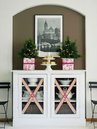 Putting ribbons on your cabinet doors makes the whole room fun and bright! More easy decor ideas: http://www.bhg.com/christmas/crafts/low-cost-christmas-projects/?socsrc=bhgpin121513easyribboncabinetflourish&page=19