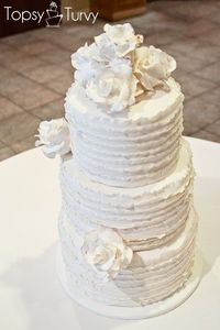this soft vintage cake has fondant ruffles around the exterior, and then extra large gum-paste roses, tipped in bronze, as a simple adornment