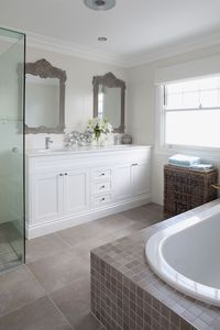 Master bathroom with twin side-by-side gray ornate bathroom mirrors paired with white double bathroom vanity with his and her sinks. White bathroom cabinets with marble countertops and polished nickel modern bathroom faucets. Seamless glass shower and soa...