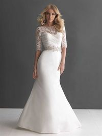 This slim gown has a soft Bateau shaped neckline in delicate lace with a 3/4 length sleeve. A Swarovski crystal band accents the natural wai...