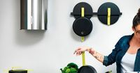 Hook pans with brightly-coloured handles that hang from a rail by Karim Rashid for cookware brand TVS.
