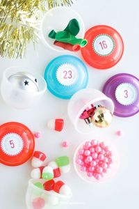 Kid's Christmas Advent Calendar...let the kids search the Christmas tree for the right little toy capsule to open: First, print and cut out the free printable. Use a 1 inch circle punch, to cut out the circles. Glue a small string of twine to the top ...