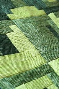 Log Cabin Blanket. Four different square patterns, alternating light, medium and dark greens within each square pattern. The finished piece is really lovely.