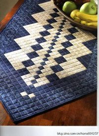 Tablerunner. Appears to be made from two different sized 4-patch blocks. Quilting grid makes it appear to be all small squares.