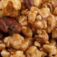 2 bags of microwave popcorn (popped) 1/2 cup butter 1 cup packed brown sugar 1/4 cup light corn syrup 1/2 teaspoon baking soda 1 cup toasted pecans or candied pecans