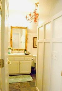 chic bathroom makeover with board and batten and chandelier, Vintage Romance featured on Remodelaholic