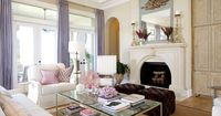 Matching brown velvet ottomans are tufted. A mix of coral and seafans and crystal sit on the coffee table.