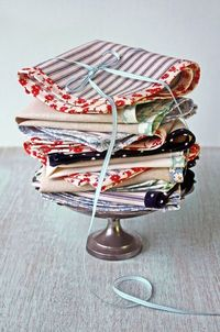 """Feedsack for the Fourth. To make these, cut 10"""" squares of material and edge with 1/2"""" double fold bias tape. You can customize the look using a bias tape maker and fabric of your choice. The bias tape shown above uses reproduction feedsack cotton..."""