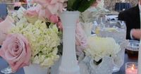Different shapes and sizes of milk glass vases with pale pink and cream flowers