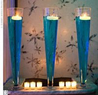 A row of candles lit up longer tables while tall vases filled with blue-dyed water and floating tea lights added drama at a bargain price.