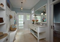 laundry/mud room - pocket door - Huge mudroom with blue paint on top part of walls and white beadboard panels on bottom part of walls framing white lacquer mirror over white washstand with shelf over cream travertine tiled floor, Cream Novana Travertine T...