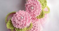 Crochet baby booties with pink flowers and pearls