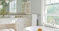 Large open bathroom with light blue walls and white cabinets and designer bathtub.