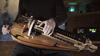The hurdy gurdy instrument for sale is a stringed instrument that produces sound by a hand wrench turned, rosined wheel scouring against the strings. The wheel capacities much like a violin bow, and single notes played on the instrument sound like those o...