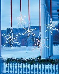 Outdoor Hanging Snowflake Ornaments. Made out of rope lights using zip ties-ribbon covers the cord.