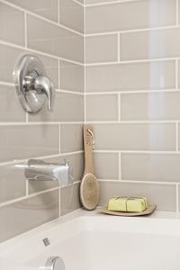 Gorgeous shower features a gray subway tile surround accented with white grout.