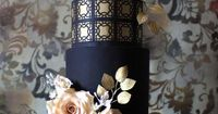 Gold and black wedding cake with peach flowers