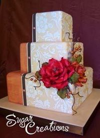 Fancy three tier square retro orange and ivory wedding cake. Decorated with white embosed wall paper like decorations along the ivory side of the cake. Garnished with a large rich red rose. From www.sugarcreations.com