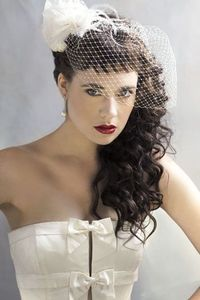 A Fifties Romance style features short baby bangs combined with textured curls, a vintage veil and red lips