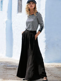 Silky wide leg trousers with snap button accents at the waistband. Pleating detail and hip pockets. Elastic waistband for easy wear.