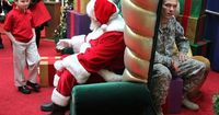 A child waits to ask Santa for his father's return from Iraq. His father is waiting behind the chair to surprise him.