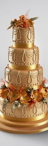 What a lavish gold wedding cake! The vintage inspired cake is decorated with sugar flowers and ribbon loops. #PANDORAloves