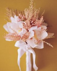 White Bouquet- Creamy Cymbidium Lionello spills out of a bridal bouquet accented by frothy astilbe and buds of society garlic, finished with white silk-satin ribbon.