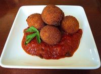 Awesome little balls of cheese, prosciutto and herbs, rolled in crumbs and fried. Served with a spicy marinara.