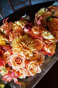 Accent roses and dahlias in complementary orange, yellow and pink hues with gloriosa lilies for a lovely arrangement.