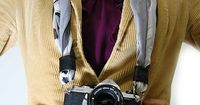 Make a camera strap from a silk scarf. easy and strong. And less bulky than a big padded strap but softer more comfy i'm sure than a thinner webbed strap.