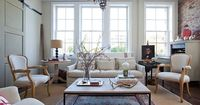 living rooms - Oriental rug layered sisal rug brickmaker's coffee table linen slipcover sofa French chairs limed oak pedestal table secretary exposed brick wall gray sliding barn door