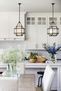Suzanne Kasler Morris Lanterns hang over a white center island topped with white quartz countertop in front of off-white shaker cabinets and white beveled subway tiles.