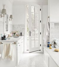 crisp bathroom. Showing the possible combo of larger marble subway tiles on the walls with a small marble tile mosaic on the floors.