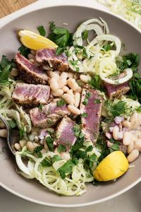 Rich tuna and creamy white beans are the foundations of a favorite warm-weather Mediterranean salad, often accented with tomatoes and onion Here, well-seasoned