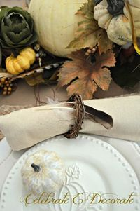 A Thanksgiving tablescape that is headed by a grapevine cornucopia whose bounty tumbles out onto the table to adorn the banquet.